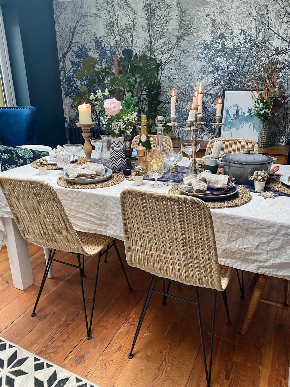 dining table set up for a christmas dinner with forest wallpaper mural and rattan dining chairs
