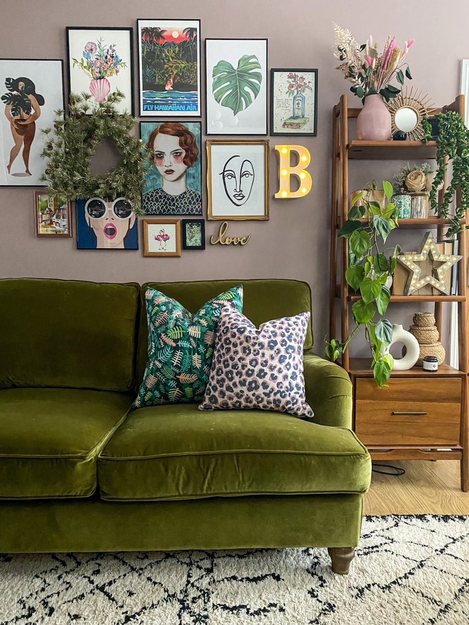 green velvet sofa with mid century bookcase from west elm, gallery wall, la redoute rug and walls painted in graham and brown spiced mulberry