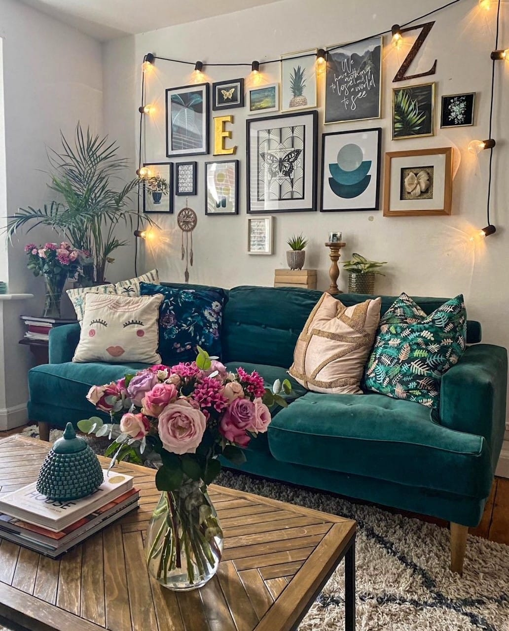 green velvet sofa in the living room with pink flowers, industrial style coffee table and gallery wall
