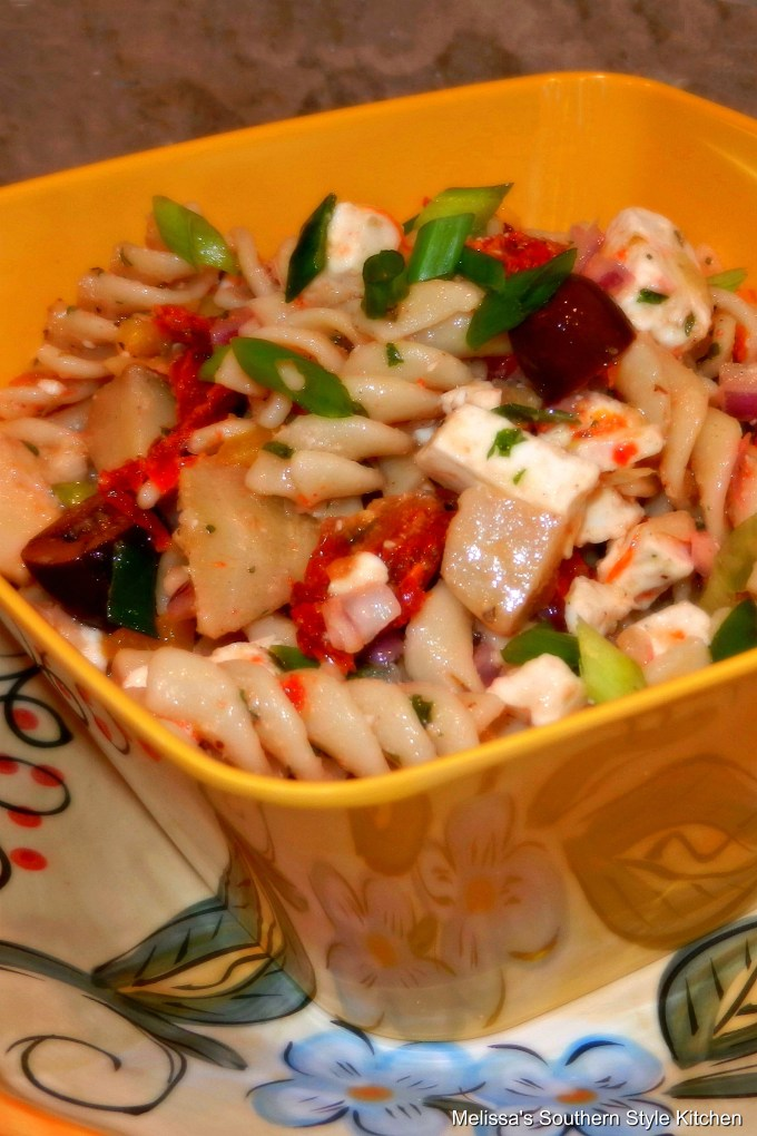 Greek Pasta Salad in a serving bowl on a plate