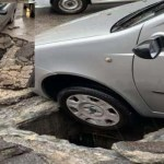 Cede il manto stradale: auto incastrata in un tombino rimasto scoperto