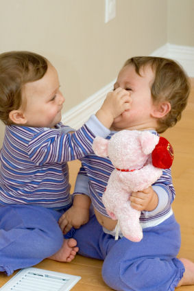 Twin toddlers fight over a toy