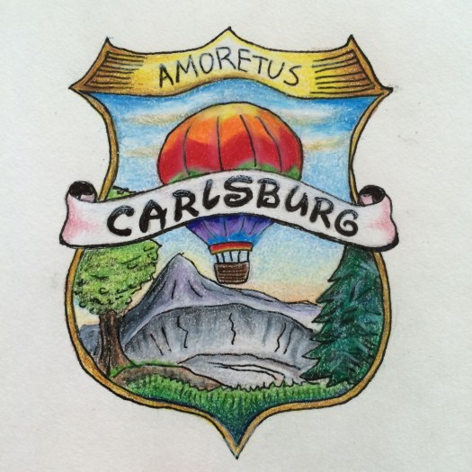 full color drawing: shield with hot air balloon, banner, volcano crater, trees