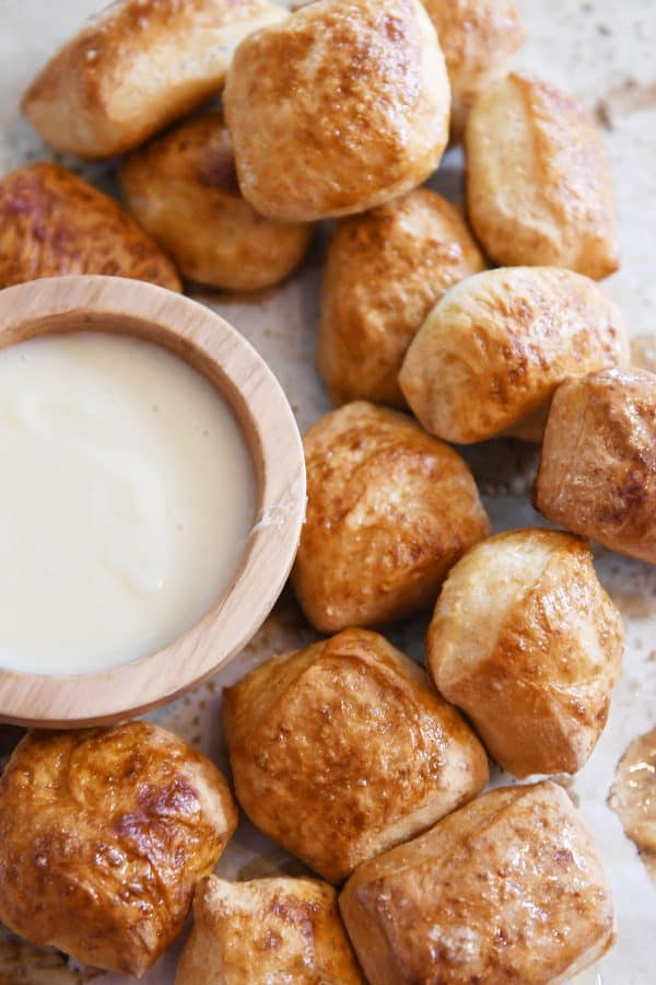 easy homemade soft pretzel bites on sheet pan with bowl of cheese sauce