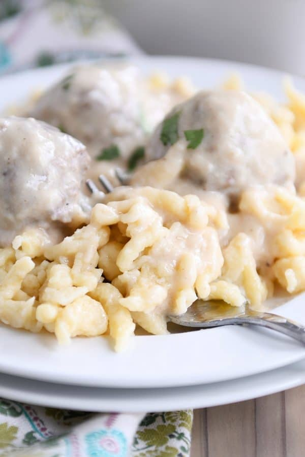 white plate with homemade German spaetzle noodles and meatballs and fork