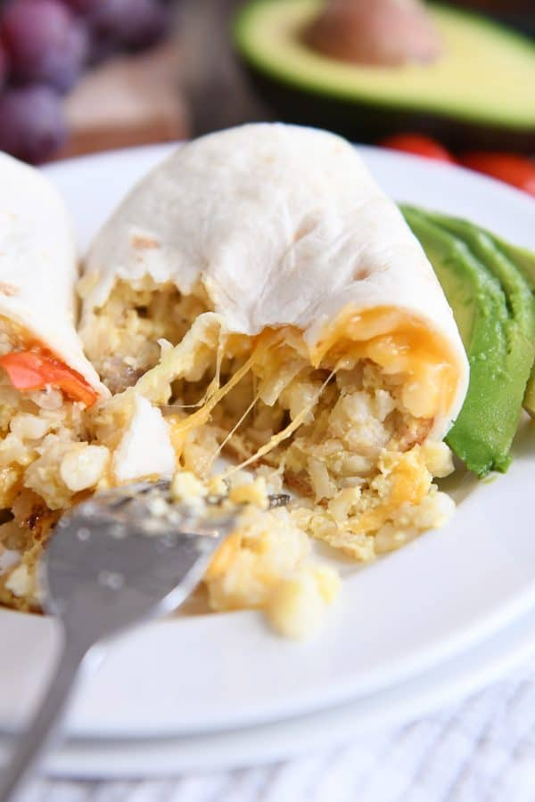 stringy cheese pulling away on easy freezer breakfast burritos on white plate