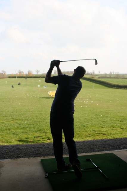 Practice your swing on the driving range.