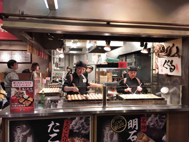 Cooks preparing takoyaki in Osaka