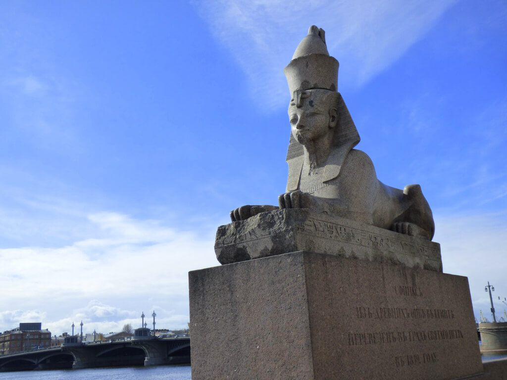A sphinx statue sitting on the banks of the river in St. Petersburg