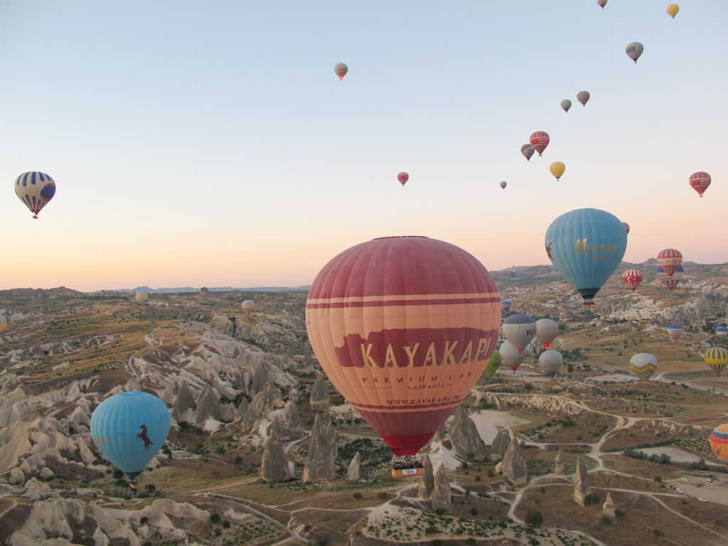 In Cappadocia Turkey, hot air balloons fill the sky at sunrise