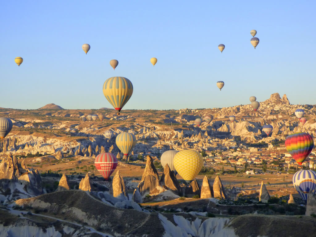 Hot air balloons next to Cappadocia's fairy chimneys