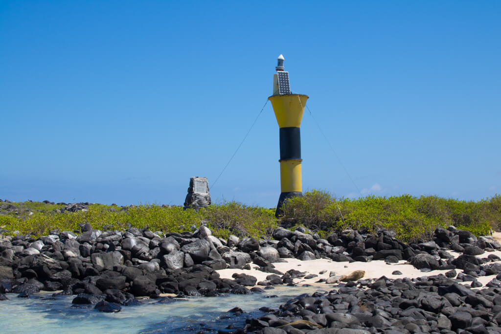 A blue and yellow lighthouse at Punta Suarez landing site on Española Island in the Galapagos