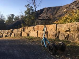 Blue Me-Mover in front of curved rock wall separating trial from embankment