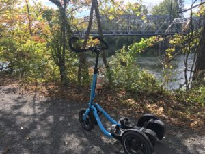 Blue Me-Mover on gravel trail with autumn leaves and truss bridge in background