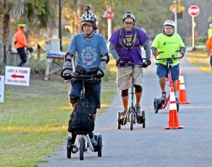 Three Me-Mover Riders on a trail with traffic cones
