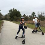 Two riders on black Trikkes on a paved trail in Florida