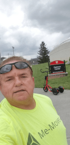 Man in a yellow shirt taking a selfie with a red Me-Mover and sign for the Dedmon Center behind him