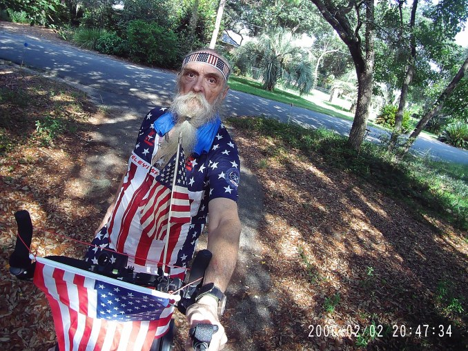 Male Me-Mover rider wearing an American flag bicycling jersey and headband, and displaying two American flags on his Me-Mover