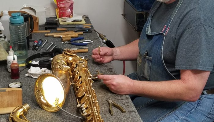 Repair technician using a light tester to check pads on a saxophone.