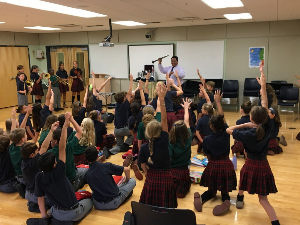Teacher holding a clarinet in front of a classroom of students sitting on the floor.