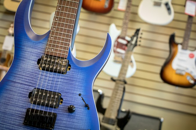 Blue electric guitar with other electric guitars hung behind it.