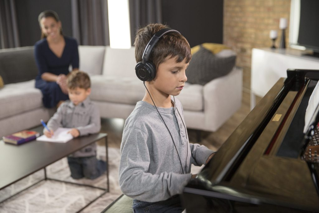 child with headphones playing piano with family in the background