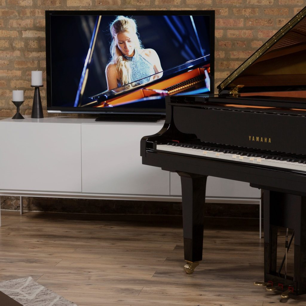 Yamaha Disklavier piano in front of television