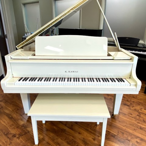 White Kawai grand piano with lid and fallboard open