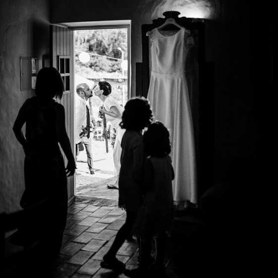 casamento aldeia de pedralva beijo dos noivos visto atraves da porta pala irmã e meninas das alianças
