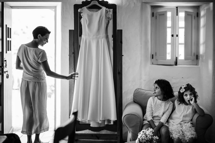 casamento aldeia de pedralva noiva observa vestido pendurado com meninas das alianças