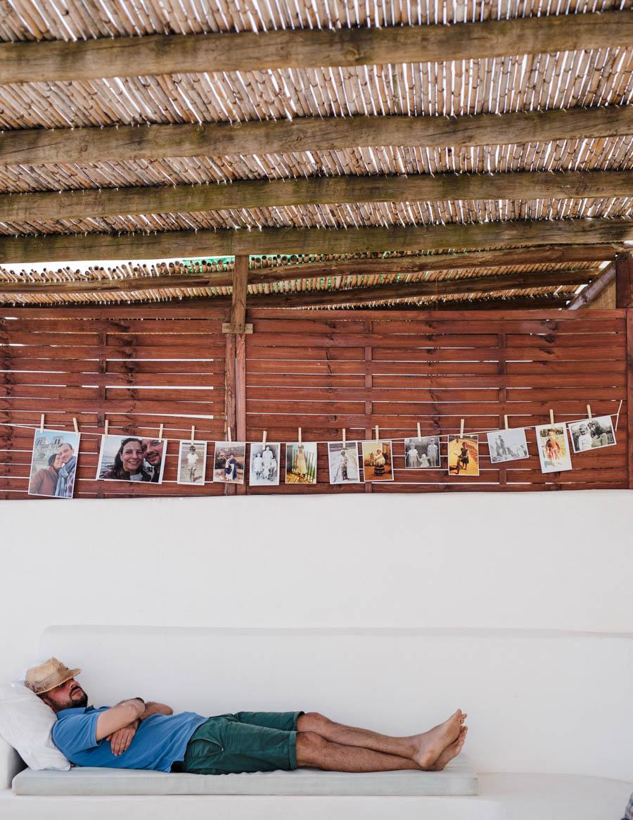 casamento aldeia de pedralva noivo dorme no pátio com chapéu na cabeça e fotografias penduradas