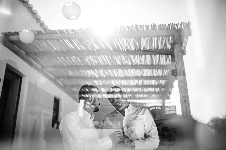 casamento aldeia de pedralva noivo e padrinho nos preparativos vistos através da janela com reflexo