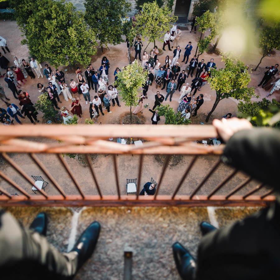 casamento gerês noivos na varanda observam convidados no pátio laranja