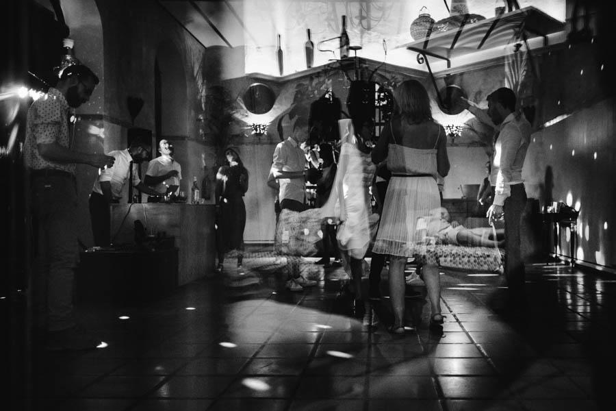 quinta de santana festa com convidados dançando enquanto menino dorme no sofá reflectido no vidro
