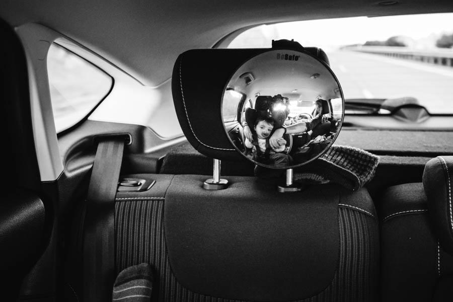 Road Trip em familia bebe mae pai maos dadas reflexo espelho carro viagem europa