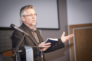 """Host church Eastview Community pastor Delbert Enns welcomes delegates and guests to Assembly 2014, saying, """"I pray you will be empowered over these next days to be changed."""" Photo by Carson Samson"""