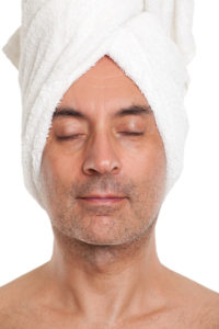 Wet towel on head for how to shave your head the right way