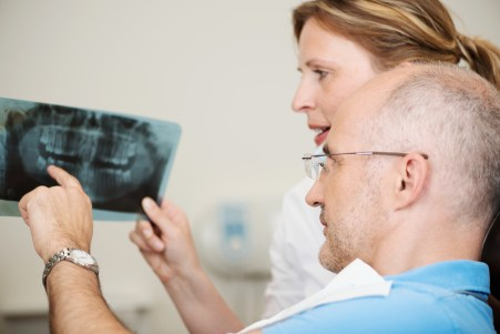 Dentist and patient are looking at x-rays