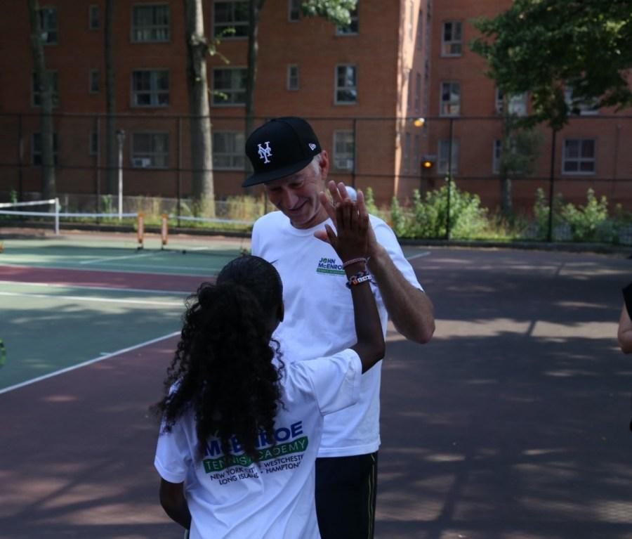 John McEnroe high fives youth tennis player at John McEnroe Tennis Academy