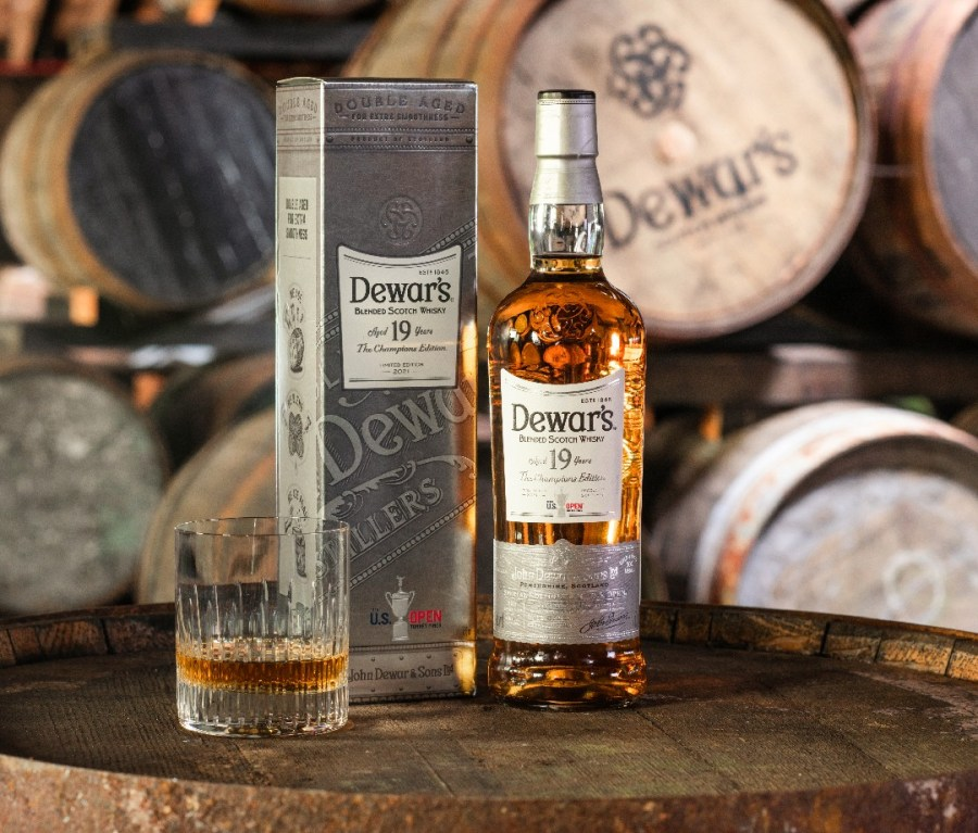 In front of whiskey casks, a box, bottle and glass full of Dewar's 19-Year-Old The Champion's Edition.