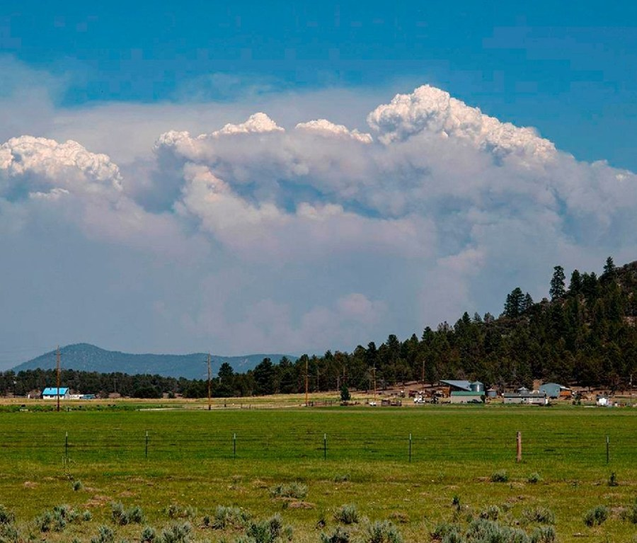 Tall plumes of smoke from the Bootleg Fire forms on the horizon of southern Oregon farmland.