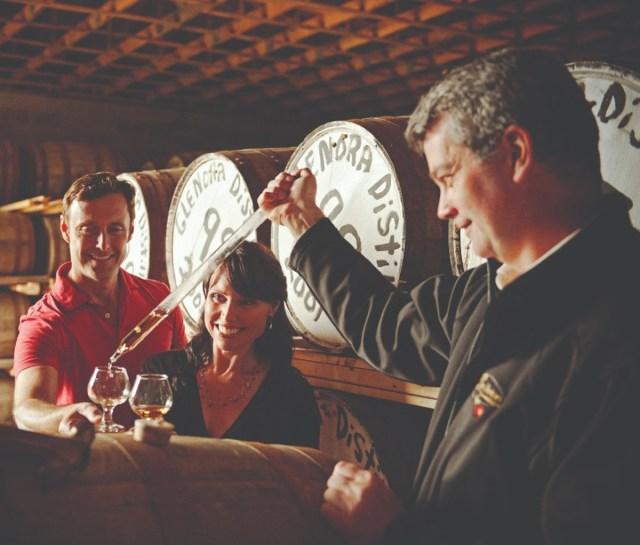 Een man geeft een stel een monster Glenora-whisky.