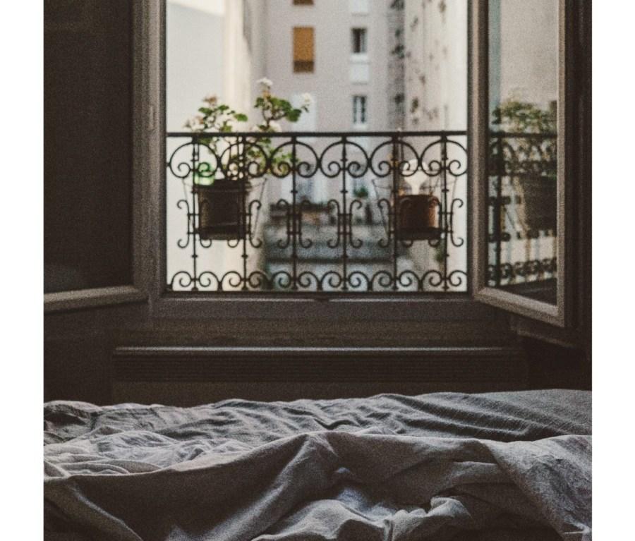 Apartment bedroom with open wrought-iron window overlooking neighboring building