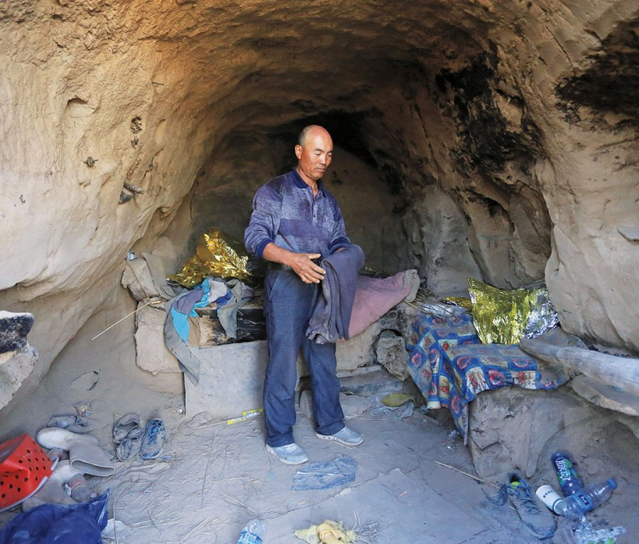 Man in cave surrounded by water bottles and debris