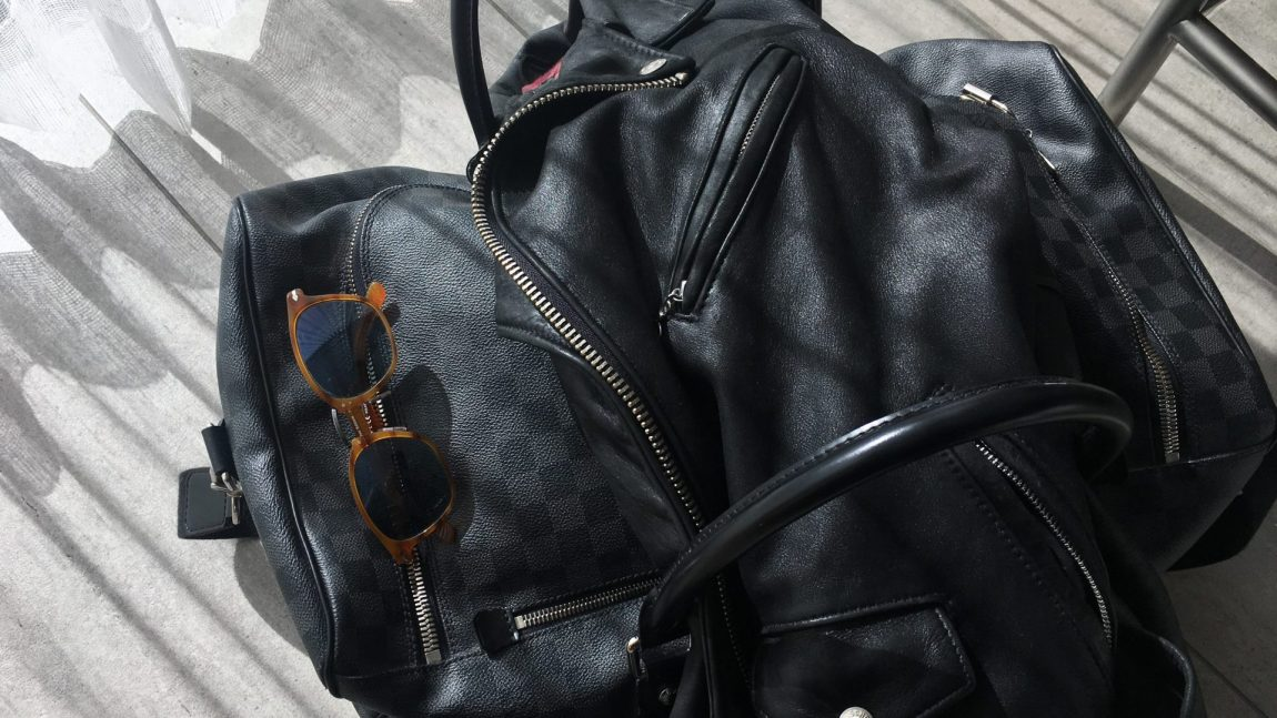 Designer Duffle Bag, Sunglasses and a Leather Biker Jacket