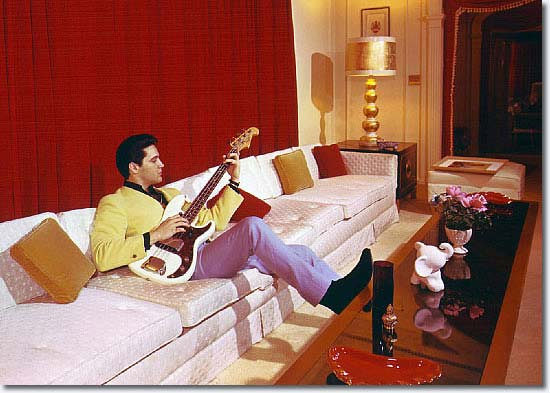 Elvis Presley wearing cool colour combinations - sitting on sofa playing his guitar