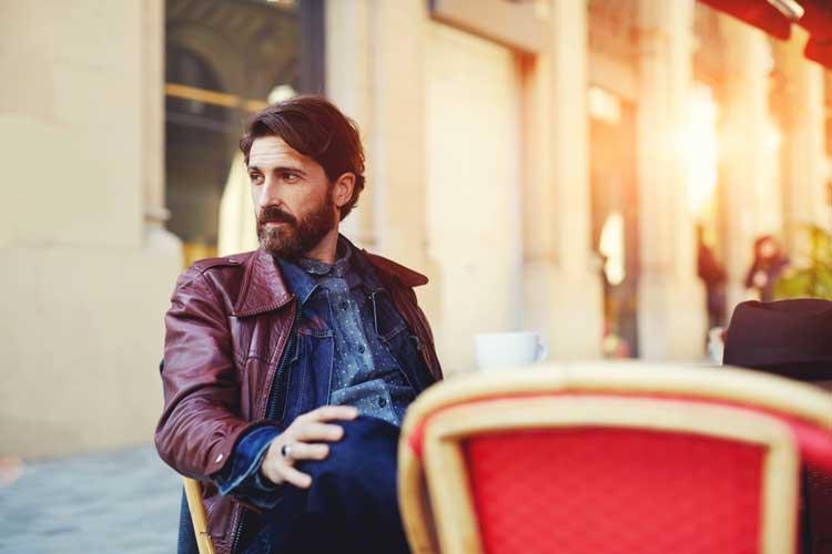 Italian men fashion sense leather jacket sitting on chair terrace