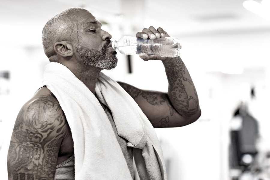 Black man drinking bottle of water