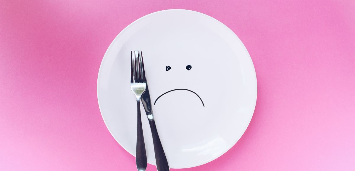 Sad face on plate with pink background. What you need to know about keto diets.