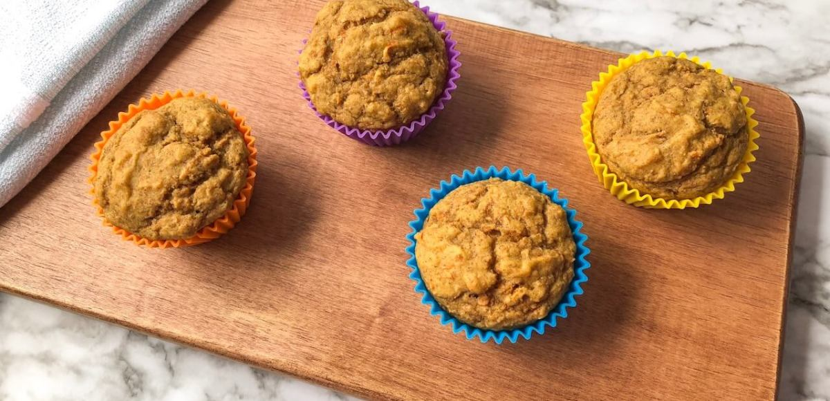 Orange carrot muffins on wooden board